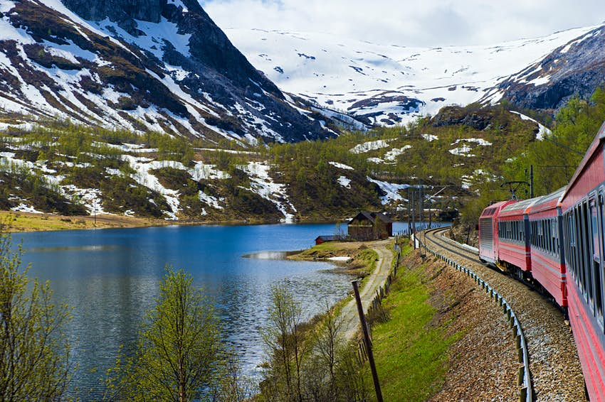 Train passes snow-capped mountains and a river from Oslo to Bergen in Norway.