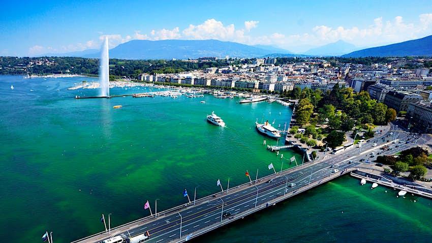 Eine Straßenbrücke überquert einen Abschnitt des Genfersees.  Die Brücke, die sich über das klare blaue Wasser spannt, wird von mehreren Autos überquert, während im Hintergrund eine kleine Küstenstadt erscheint.