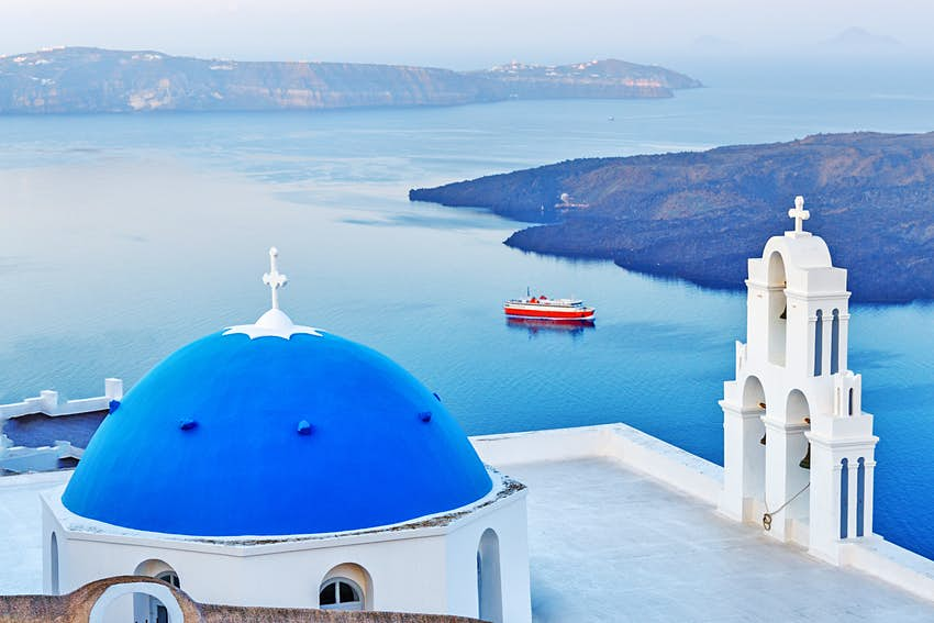Blue dome church of Santorini island, Greece, Fira village. Island and moored red ferry in background, Morning scenery.