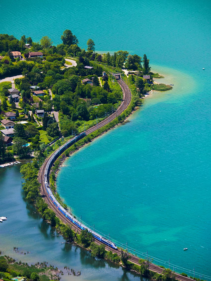 An aerial view of a train line with a bridge over a body of water