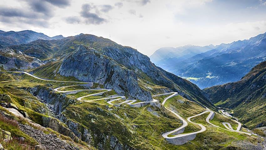 Eine Straße, der Gotthardpass, ragt in der Schweiz einen Berg hinunter und tötet sich mehrmals.  In der Ferne waren weitere Berggipfel zu sehen.