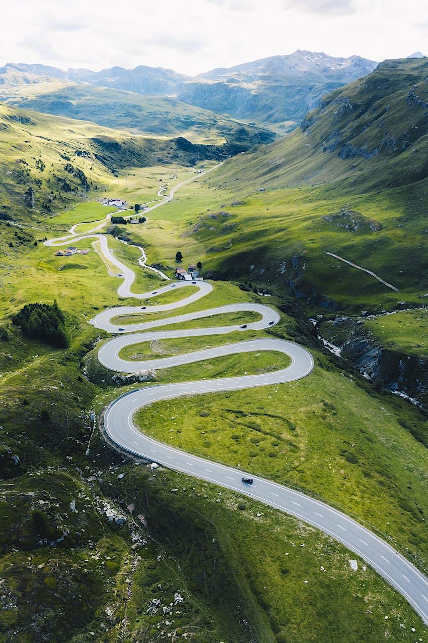 Drohnenaufnahme der Straße mit scharfen Kurven im Sommer in der Nähe des Gulier-Passes.  Die Straße liegt mitten in einem grasbewachsenen Tal mit hohen Bergen auf beiden Seiten.