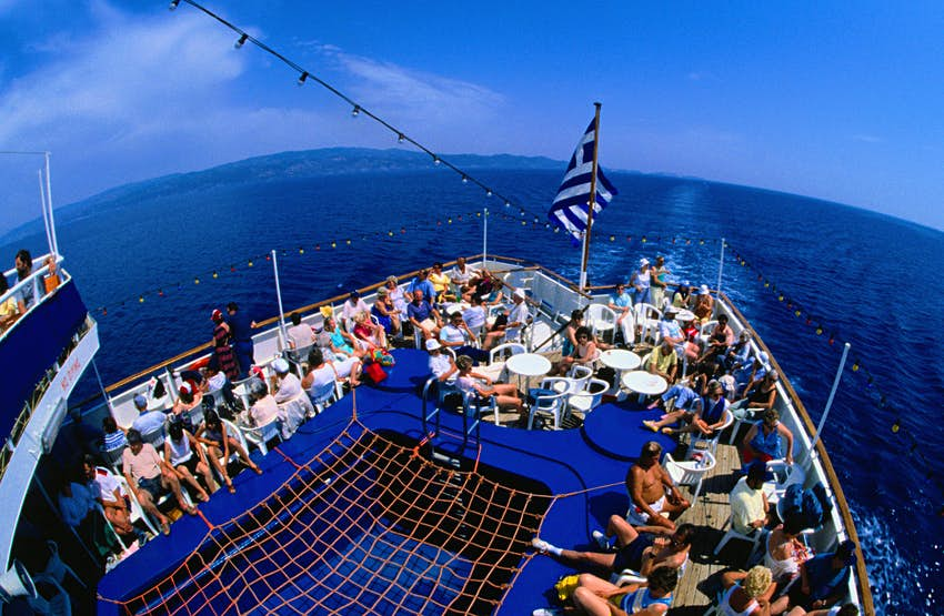 Crowds of people relax on the back deck of a large ferry sailing on the Aegean Sea, Greece.