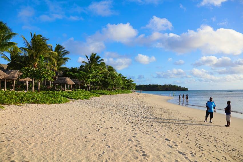 A wide section of sandy beach is backed by palm trees and lapped by blue water. A couple of rustic bungalows are visible amongst the palms behind the beach, while a few people paddle in the calm waters.