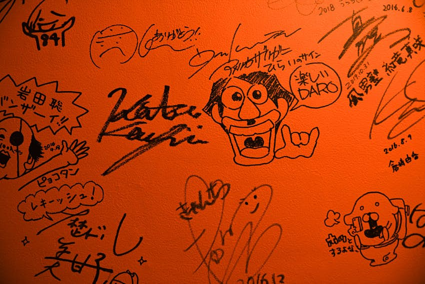 Autographs signed on a bathroom wall inside 84