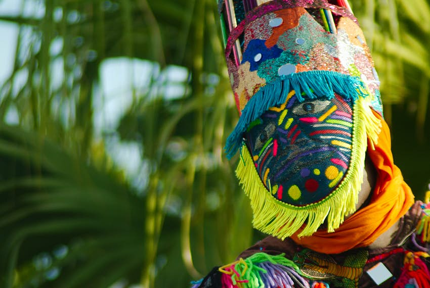 a man in a colorful mask with palm trees in the background