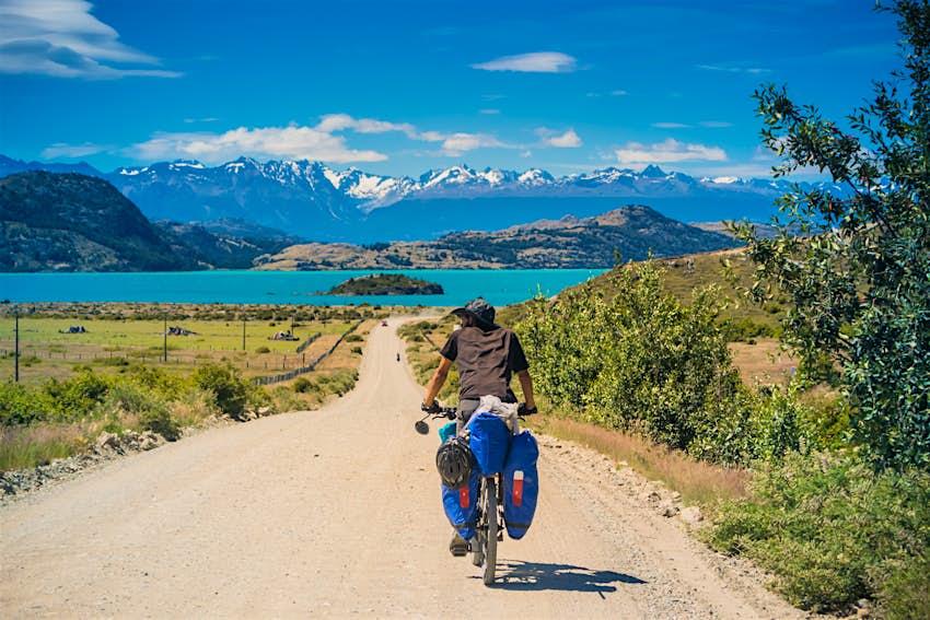 Un ciclista Tourer va hacia el lago azul y las montañas grises en el camino de tierra de la Carretera Australiana Carrera.