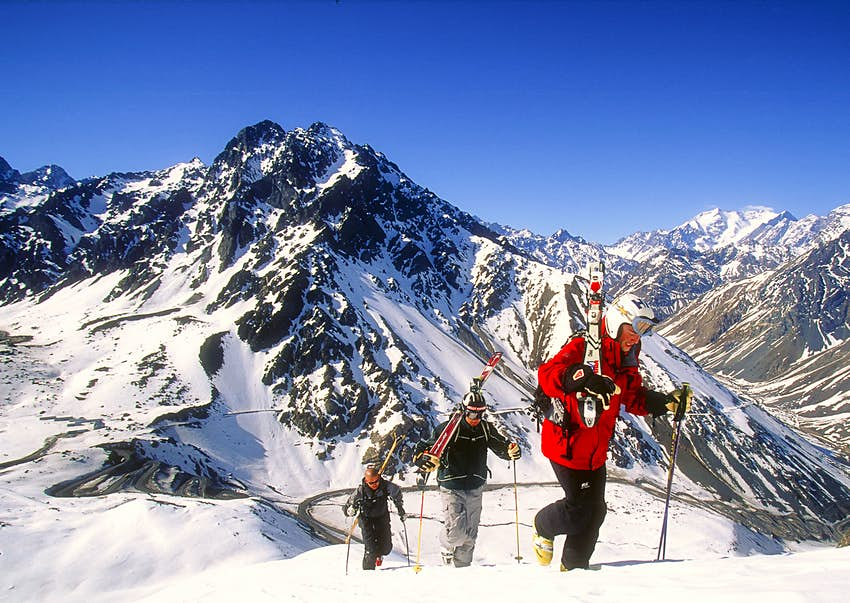 Con el telón de fondo de Portillo, un popular centro de deportes de invierno en la Cordillera de los Andes de Chile, un grupo de esquiadores para la nueva nevada con los hombros sobre los hombros