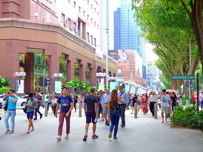 A crowd of people walk along Orchard Road on a sunny, blue-skied day in Singapore with a tall glass skyscraper rising up in the background.