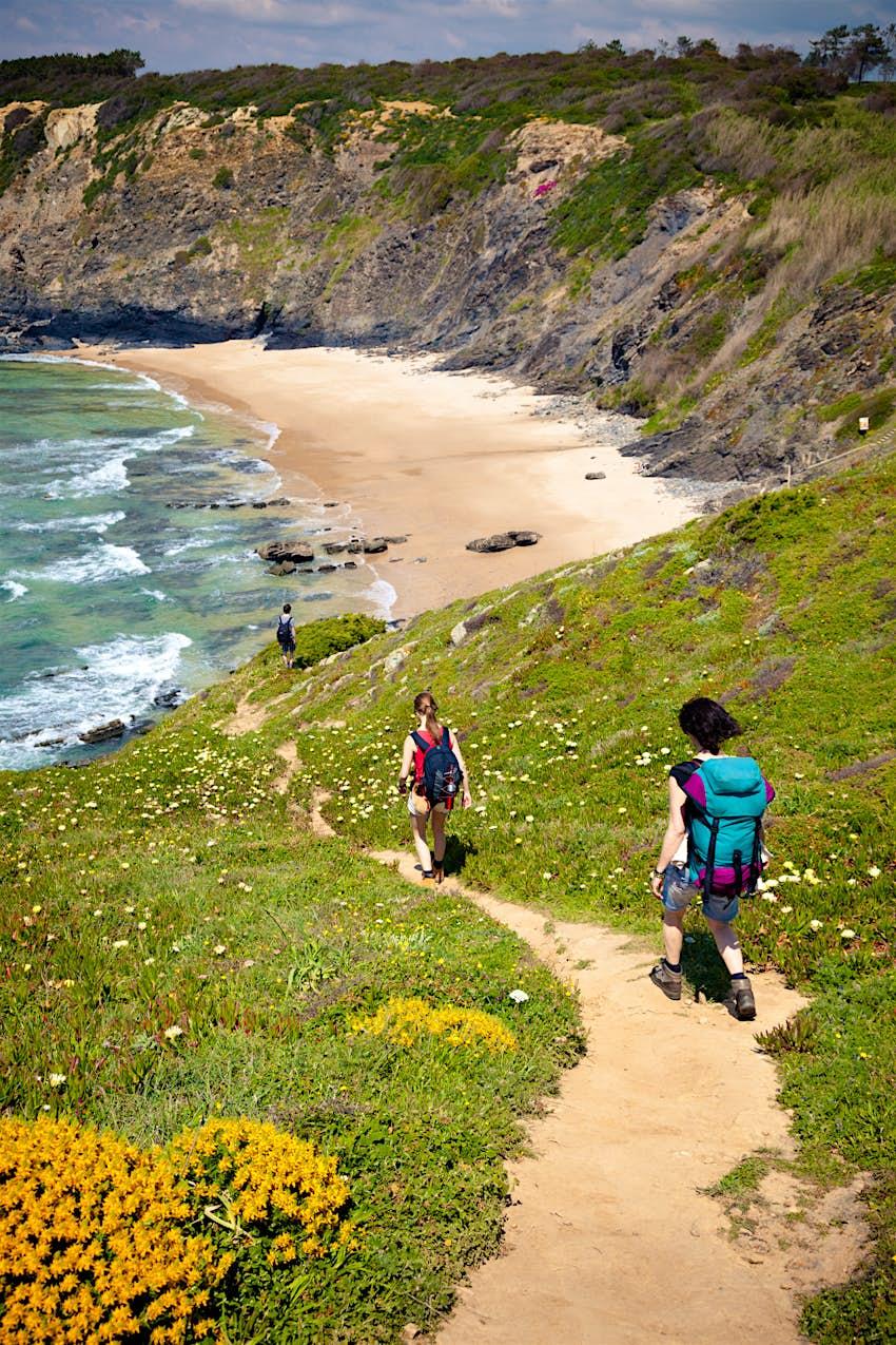 Duas mulheres caminham por um trecho de costa no topo de uma falésia da Rota Vicente. Na frente deles está uma ampla praia de areia.