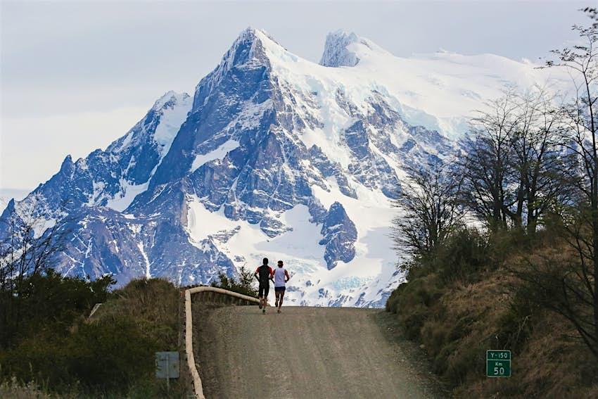 Los atletas que corren durante el Maratón Internacional Patagonia corren por la cresta de una carretera, con enormes montañas cubiertas de nieve al fondo.