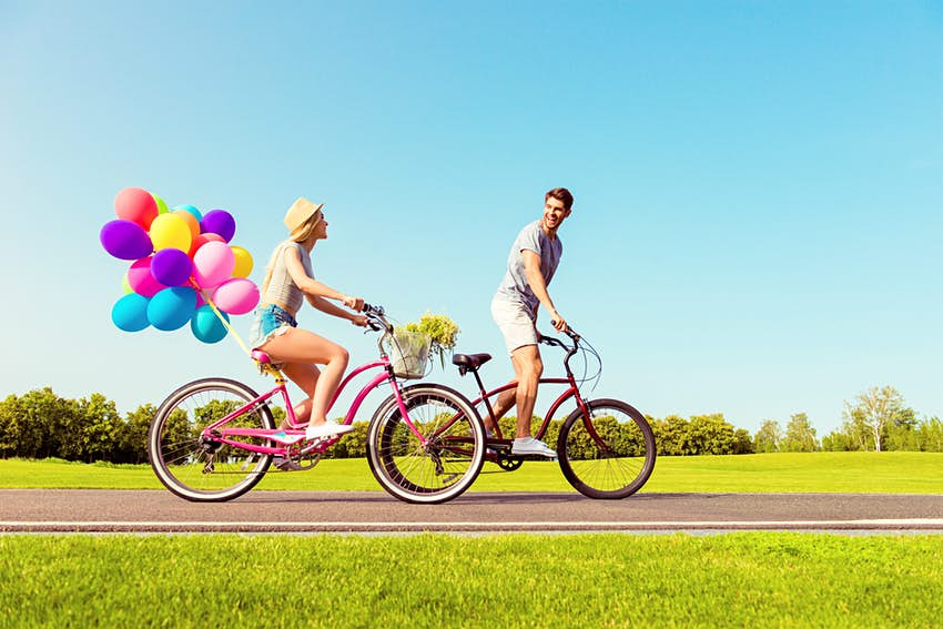A man and a woman cycling down a road in the blazing sunshine. The woman's bike has multcolored balloons tied to the back of it