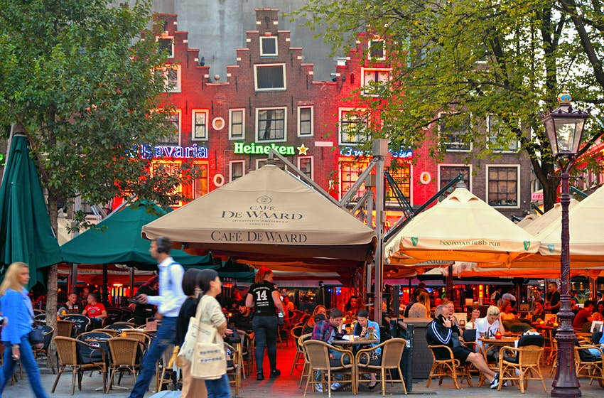Les gens se sont assis dehors dans des restaurants et des bars sous des auvents devant des bâtiments hollandais traditionnels