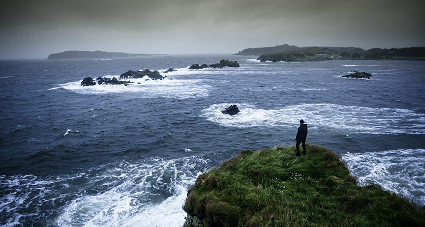 Woman standing on a cliff facing the sea on the Isle of Islay, Scotland