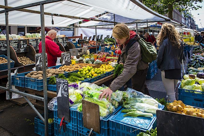 Les gens à un étal de marché animé rempli de fruits et légumes