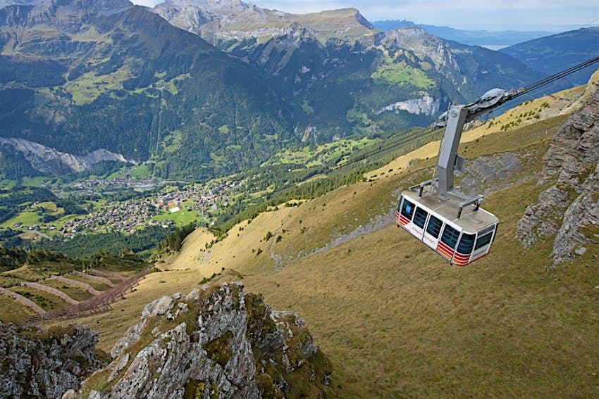 Die Seilbahn hängt hoch über dem Lauterbrunnental in der Schweiz.  Unten sind bewaldete Hänge sichtbar.