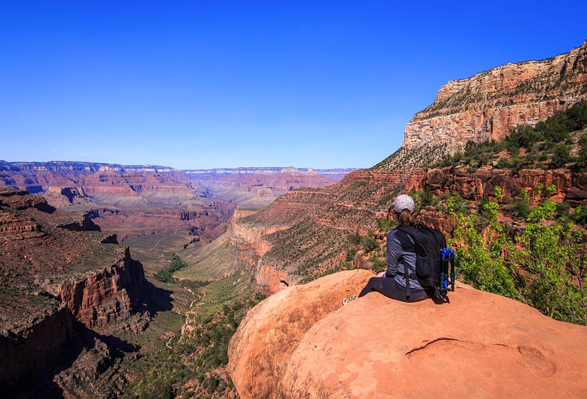 A woman sits on a rock overlooking a deep canyon
