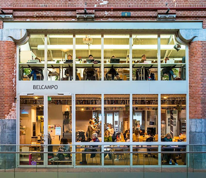 Une grande série de fenêtres dans un ancien bâtiment industriel avec des gens à l'intérieur assis devant des ordinateurs portables ou des tables