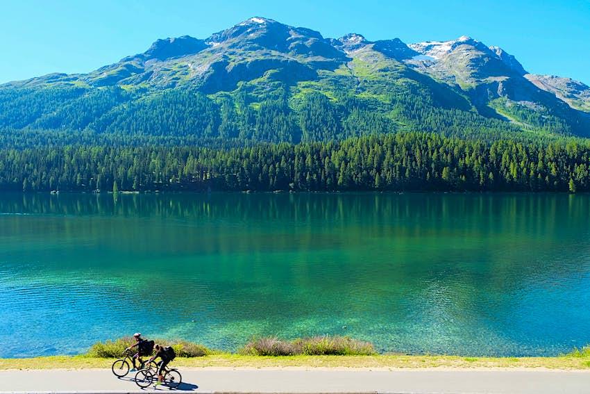 Radfahrer entlang einer Uferstraße in Lugano, Schweiz.  Hinter dem großen See sind Berge zu sehen.