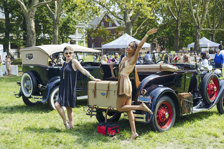 Two women pose by a car at The Jazz Age Lawn Party on Governors Island