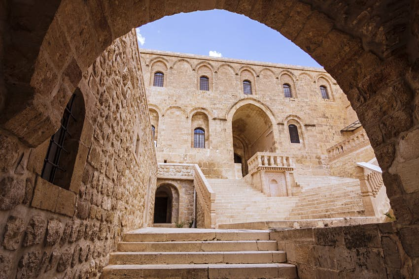 A sandstone-colored monastery building viewed through an archway