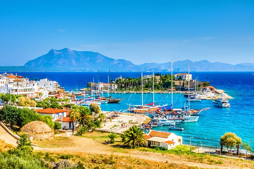 Boats moored in a small harbor on a peninsula surrounded by turquoise seas