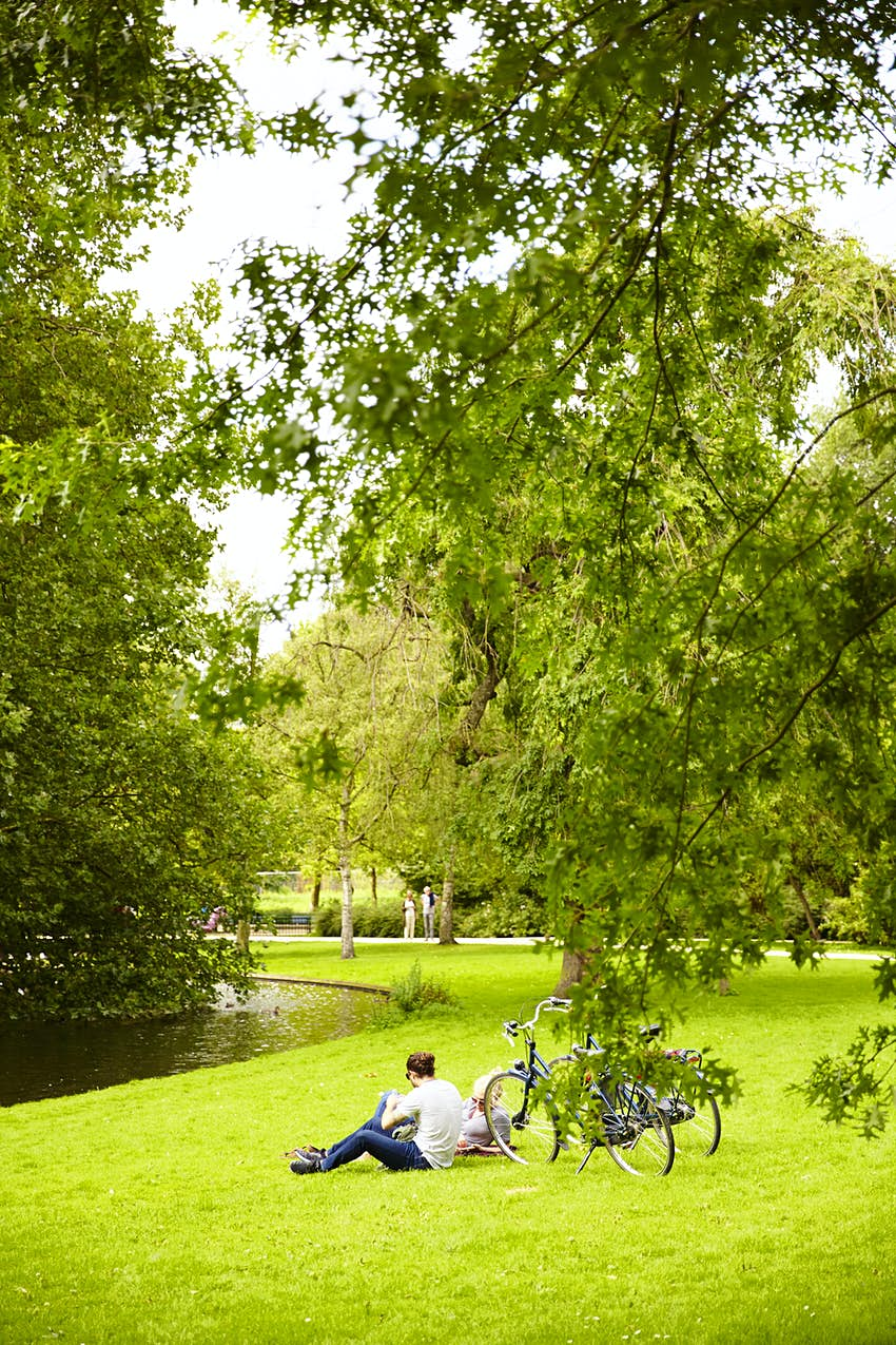 A couple lie on the grass near their bikes in a park with a small stream nearby
