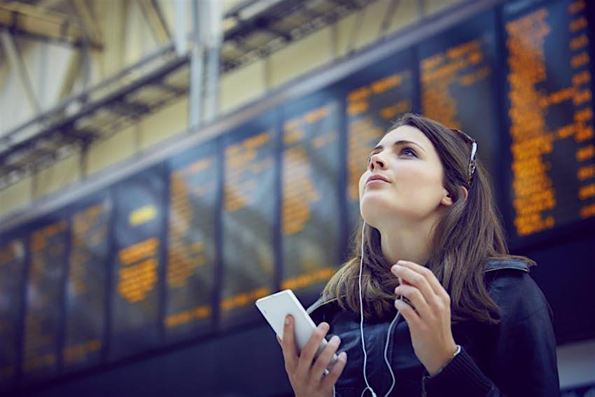 Woman looking at departure information, London, UK