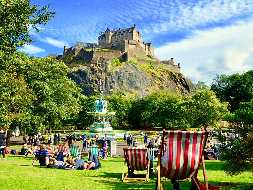 August 2018: People relaxing near Ross Fountain in Princes street gardens, with Edinburgh Castle above.
