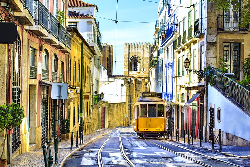 Empty Lisbon street with an iconic yellow tram and the bell tower of Lisbon Cathedral in the background.