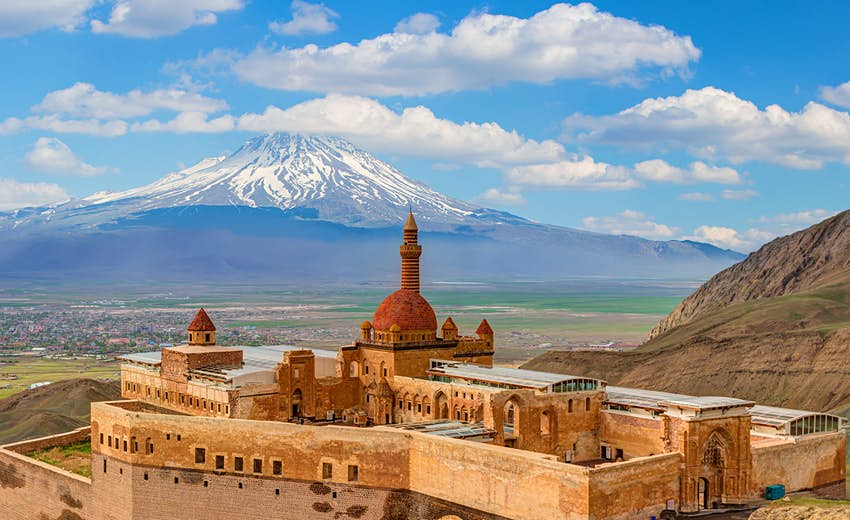A red-stone palace with a central domed tower. A snow-capped mountain rises in the distance