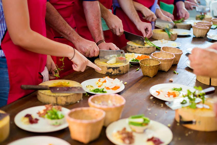 Participants prepare Thai dishes with carving knives during a cooking class in Chiang Mai.