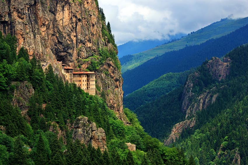 A monastery building built into the side of a huge cliff high up above a valley