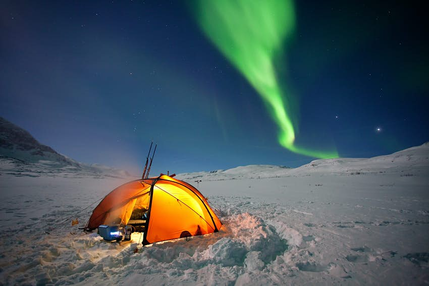 A tent in a snowy field illuminated at night under the Northern Lights.