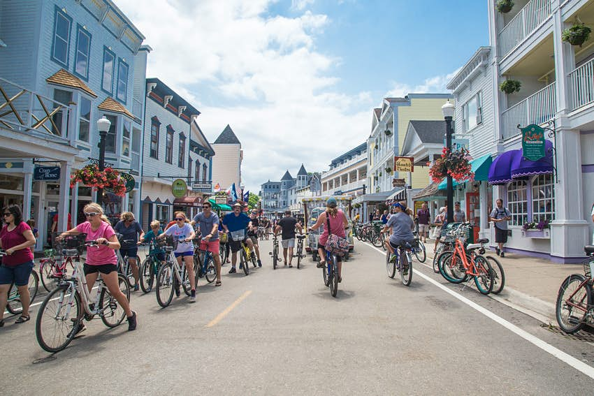 A pedestrian street lined with young and old cycling