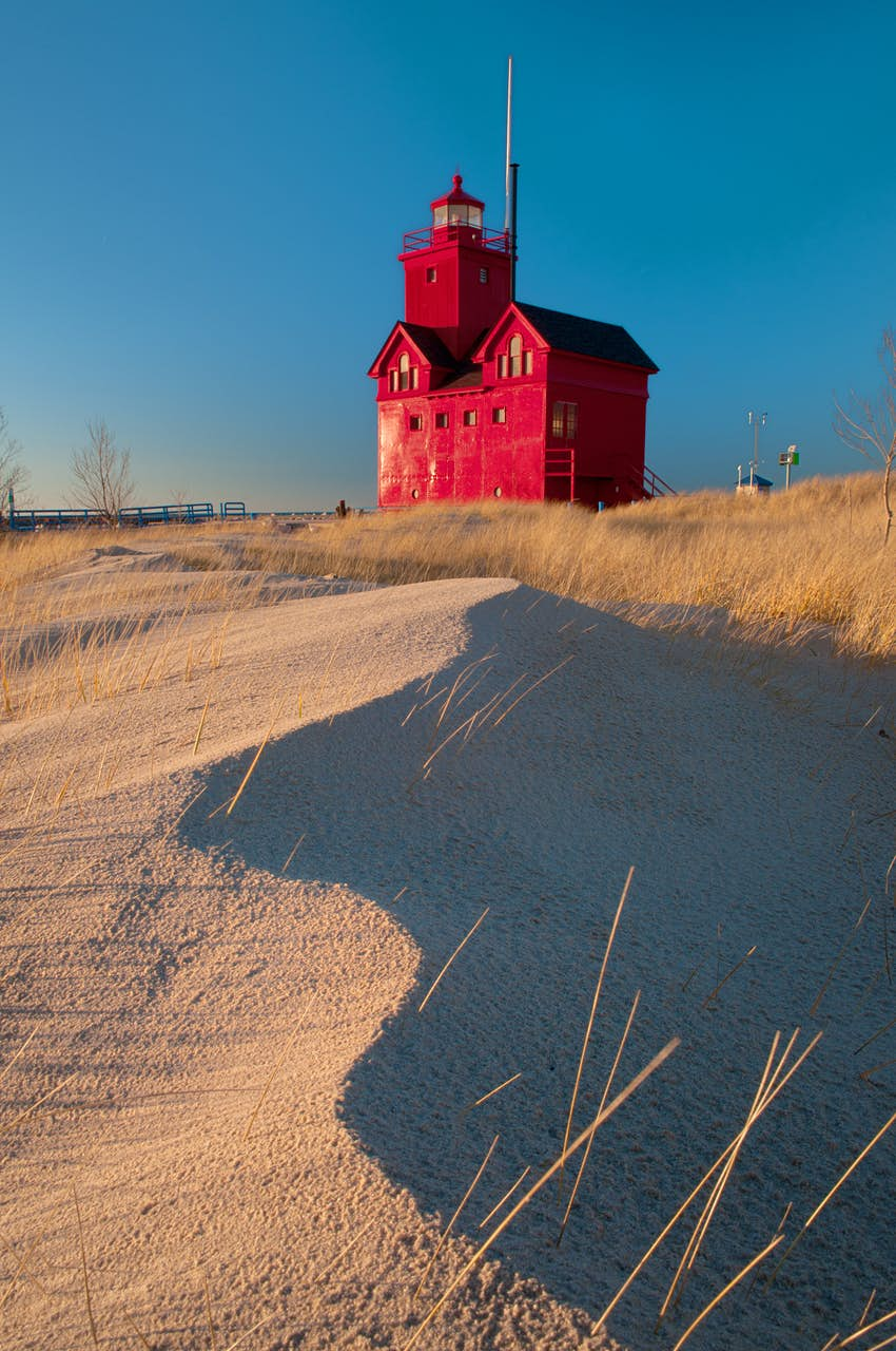 A red wooden building stands on top of the sand dunes