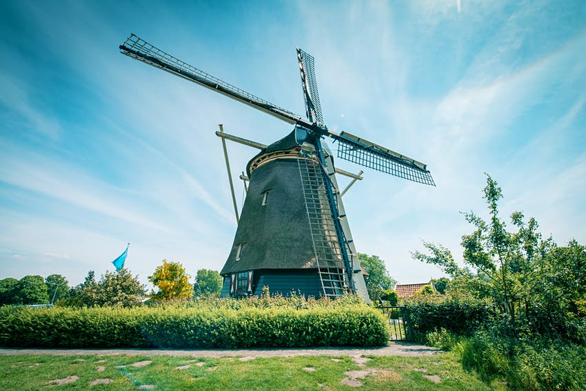 A traditional wooden Dutch windmill in a park
