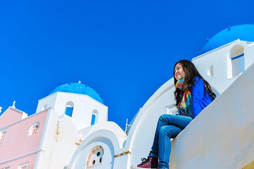 Η μόνη γυναίκα που κάθεται στην άκρη της στέγης στη Σαντορίνη, Oya, Ελλάδα