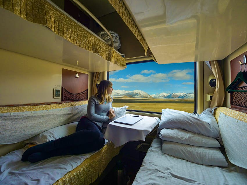 Young woman lies on the bed and looks through the window of the sleeper train crossing picturesque Tibet. Female tourist observing the landscape while traveling along the Trans-Himalayan railway.