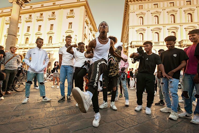 Unidentified B-boy break dancers perform in the street for the crowd. Hip Hop battle at an informal street dance meet.