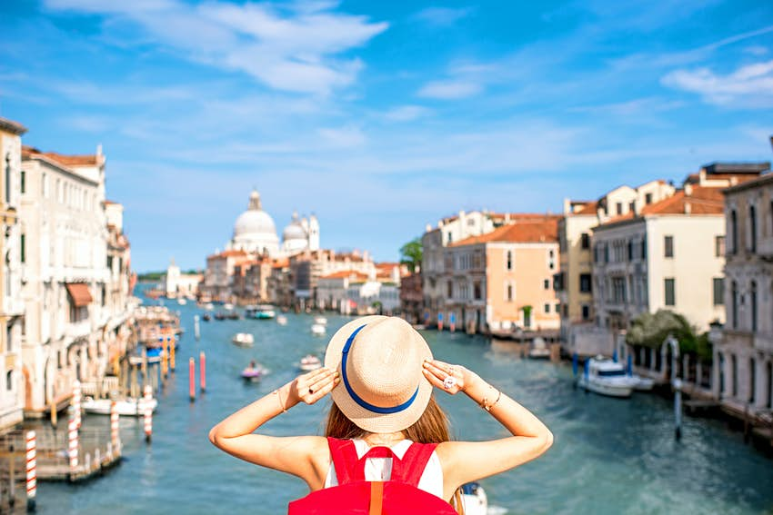 A woman stands on a bridge in Venice and admires the view of the Grand Canal.