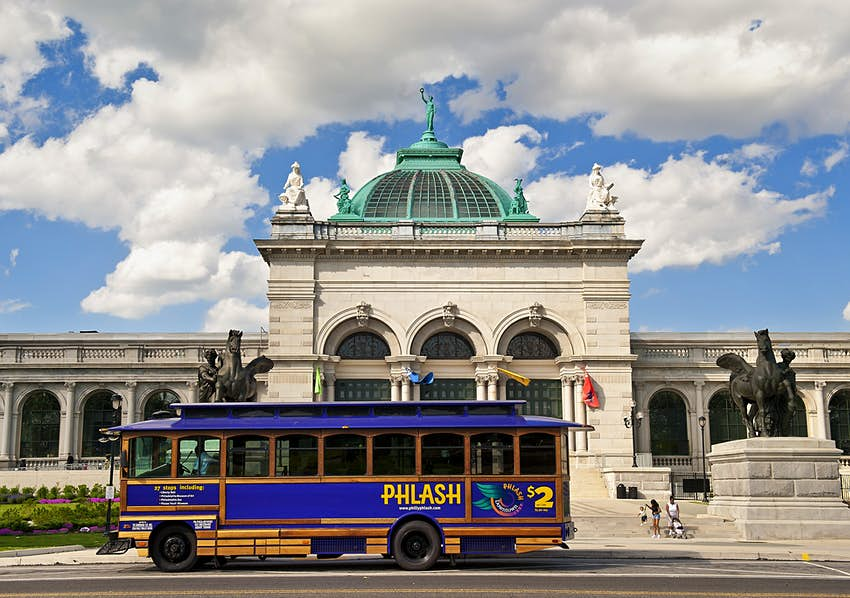 The purple PhillyPHLASH trolleybus passes the Please Touch Museum on a cloudy day in Philadelphia.