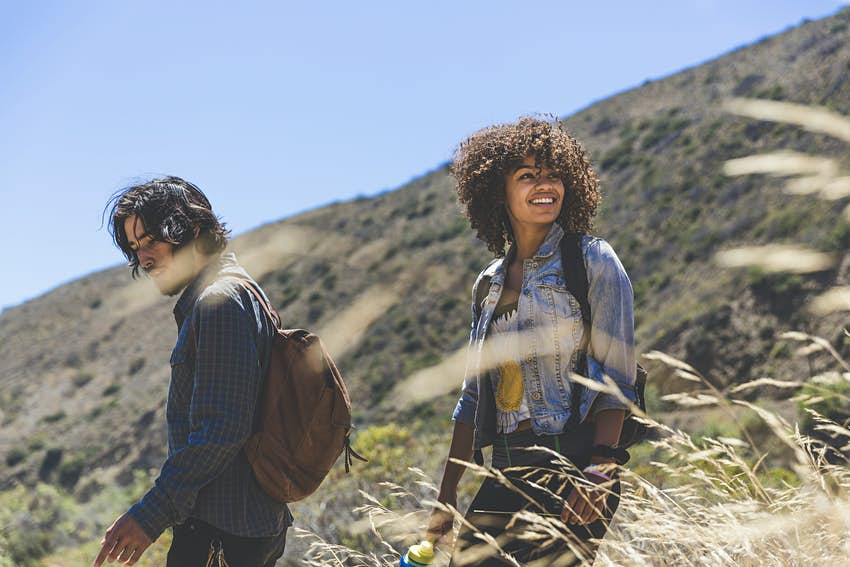 Smiling young woman hiking with boyfriend on sunny day