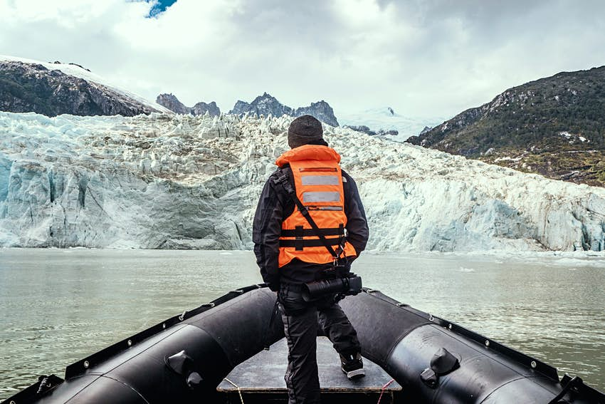 Man standing on a boat looking at the glacier