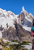 A woman in maroon pants and a teal shirt stands looking at El Chalten in Argentina