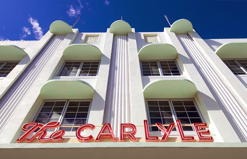 facade of the Carlyle, an art deco hotel in Miami, on a sunny day