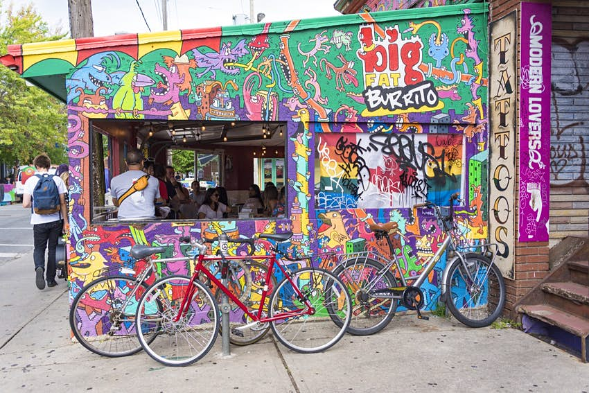 Bicycles parked beside big fat burrito outlet in Kensington Market, Toronto