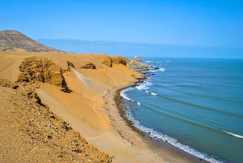 A coastline buttressed by large golden dunes and rock faces © marcosvelloso / shutterstock