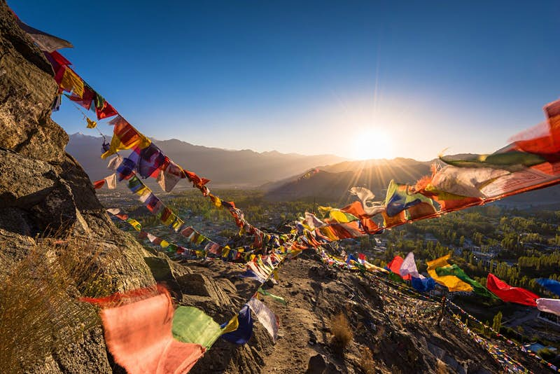 Prayer flags blowing in the wind at sunrise above the town of Leh in Ladakh, India