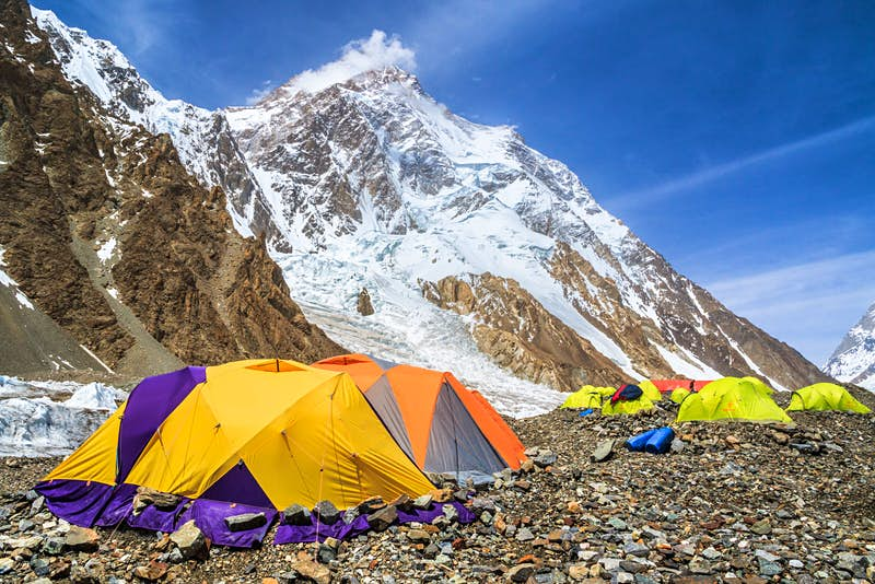 A number of colourful camping tents at K2 base camp. With the snowy summit standing in the background.